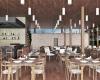 vista interna do restaurante com mesas piso e forro em madeira