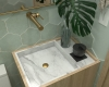 detalhe da bancada do lavabo em mármore e madeira e torneira dourada de parede