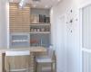 varanda gourmet pequena com revestimentos na parede e duto da churrasqueira em porcelanato que imita madeira e azulejo cinza apartamento talipo campinas