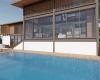 piscina e deck de madeira vista dos fundos da residencia em estrutura metálica em terreno com declive acentuado