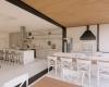vista da área gourmet integrada à cozinha, forro em madeira, piso claro e bancada em mármore